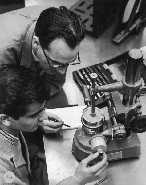 Two engineers use a precise measuring device to correctly ascertain the width of a circular metal ring. Photograph by Heinz Zinram