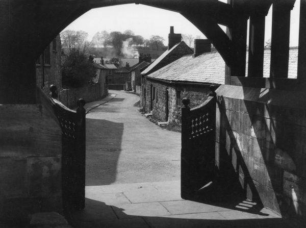 A charming view of the village street of Bramham, Yorkshire, England, seen through the lychgate of its ancient church. Date: 1950s