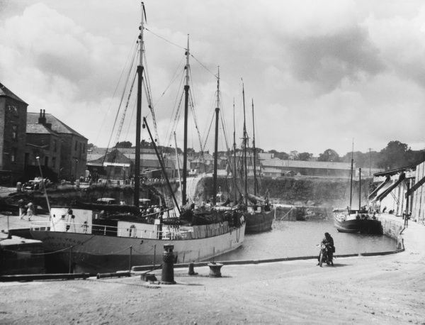 The small but busy harbour of Charlestown, a quaint little Cornish sea port. The local industry is devoted entirely to the shipping of china clay to all parts of the world