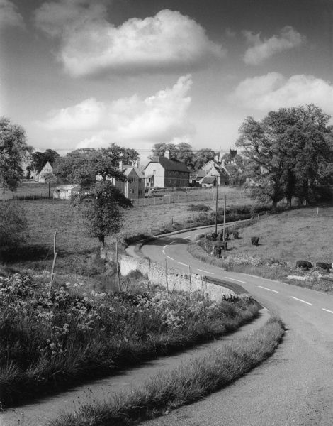 The winding road into Church Enstone, a picturesque village in Oxfordshire, England. Date: early 1960s