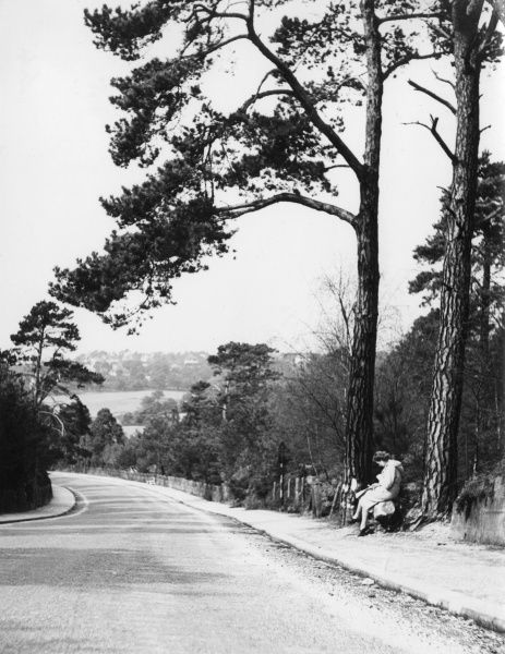 A woman sitting at the side of the road at Parkstone, Dorset, England. Date: April 1940