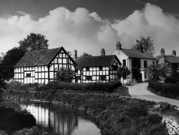 A glimpse of the charming village of Eardisland, Herefordshire, with its charming black and white timbered houses and the River Arrow running serenely by. Date: 1950s