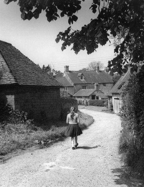 A little girl walking home from school down a country lane in the village of Farnborough, Warwickshire, England. Date: early 1960s