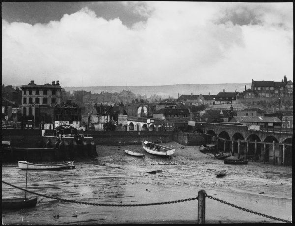 Low tide at Folkestone Harbour, Kent, England on rather a dreary old day. Date: 1940s