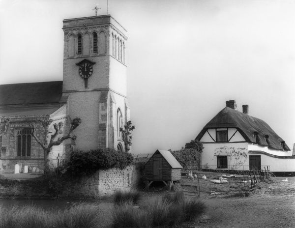 The old church and thatched cottages at Haddenham, Buckinghamshire, England. Date: early 1960s