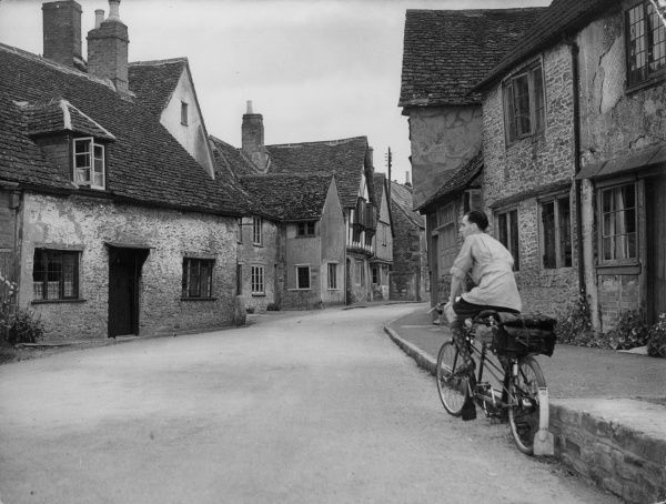 This lucky lone cyclist has the whole of this quiet village to himself. It is Lacock, Wiltshire, a perfect example of Tudor England, with its timbered houses. Date: 1930s
