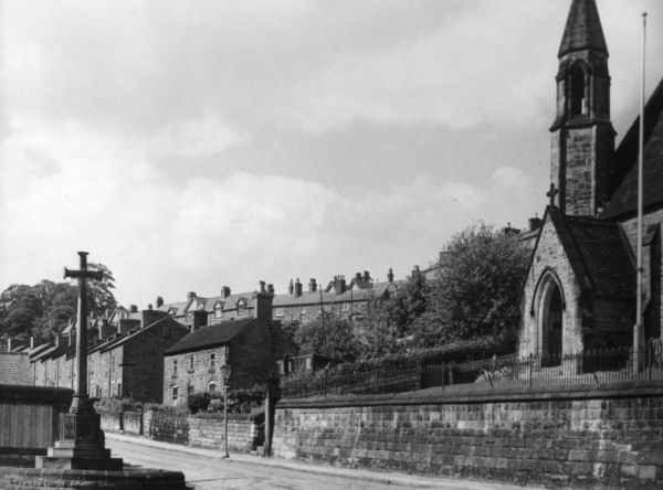 Milford, Derbyshire, England, with its stone houses, memorial cross and church. Date: 1930s