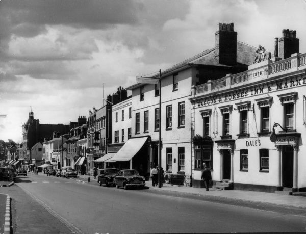 A glimpse of the High Street, Newmarket, Suffolk, England, showing the Waggon and Horses Inn (built 1868). Date: 1950s