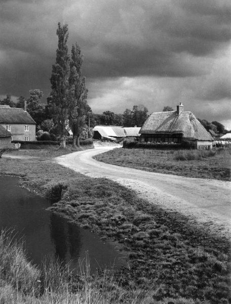 Thunder clouds over the village of Pamphill, near Wimborne Minster, Dorset, England. Date: 1950s