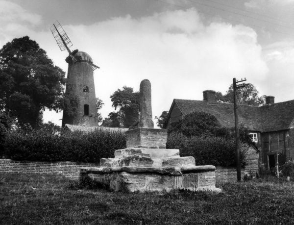 The fine old windmill (built 1830) and stone cross in the village of Quainton, Buckinghamshire, England. Date: 1940s
