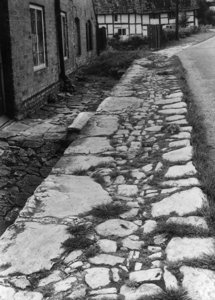 At Quainton, Buckinghamshire, England, is this fine example of a cobbled pavement, extremely rare, in these days of asphalt and concrete. Date: 1950s