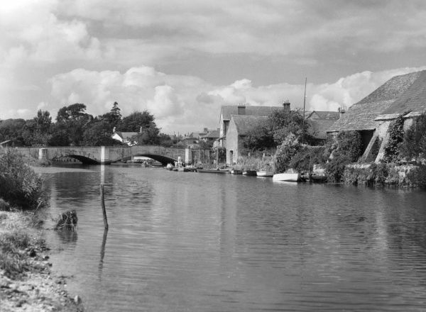A scene on the River Frome, with the riverside houses and the old bridge at Wareham, Dorset, England. Date: 1960s