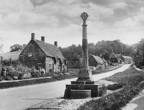 The charming village of Rockingham, Northamptonshire, on the edge of Rockingham Forest, with its stately cross and grass-bordered street winding up the hill