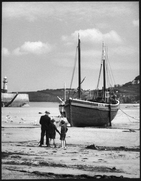 Two little boys keep their grandfather company while he finishes off his painting of a fishing trawler, on the beach near the harbour of St. Ives, Cornwall