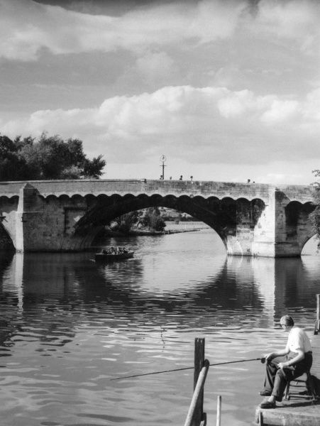 Am old man fishing beside the bridge spanning the River Ouse, St. Neots, Cambridgeshire, England. Date: 1950s