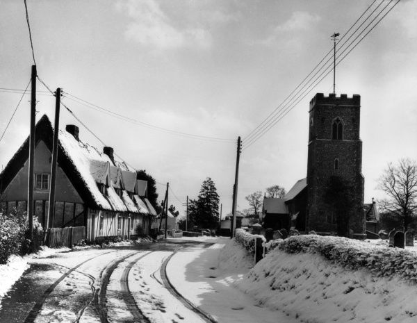 A winter scene beside the church at Tattingstone, a village between Ipswich and Manningtree, Suffolk, England. Date: 1950s