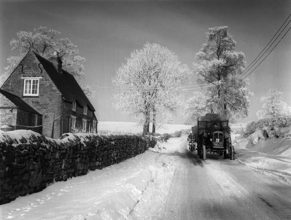 A snowy winter scene in Upper High Street, Harpole, Northamptonshire, with a tractor and trailer laden with food for cattle. Date: 1960s