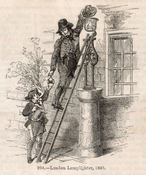 A London lamplighter on his ladder refills a street lamp with the oil which his assistant passes to him