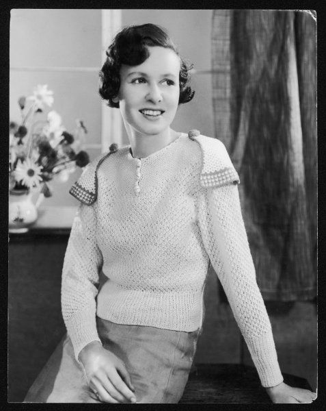 A hand-knitted jumper in a lacy stitch with round neck line & 3 button fastening. An unusual touch is the triangular shaped epaulettes attached with knitted buttons