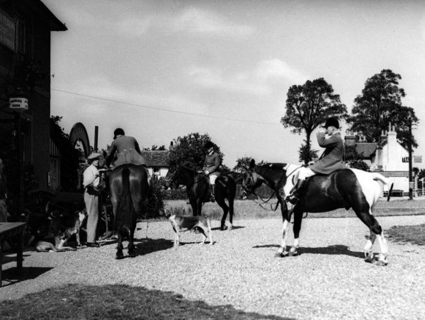 Hunt riders and their hounds meet for refreshment outside a pub at Epping Green, Essex, England, before the fox hunt. Date: 1930s
