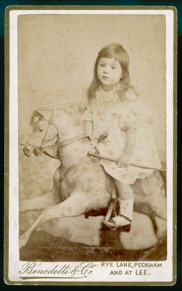 Little Eric James aged 3 wears a frilly frock, socks & shoes with a bar across the ankle as he sits astride a rocking horse. His hair is long with a fringe