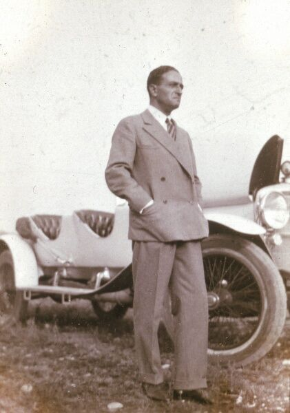 ERNST DRYDEN Poster artist, fashion pioneer and Hollywood costume designer. Standing in front of a car