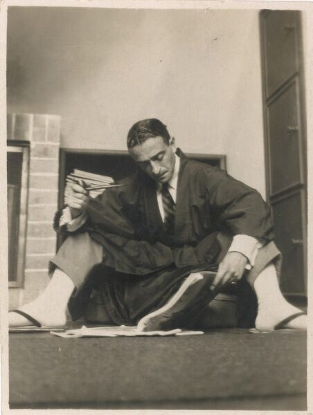 ERNST DRYDEN Poster artist, fashion pioneer and Hollywood costume designer. Sitting on the floor smoking a pipe