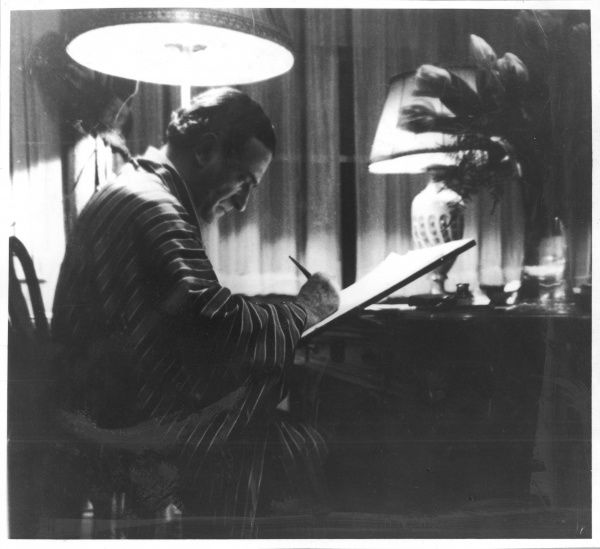ERNST DRYDEN Sketching at his flat in Neuilly, Paris, circa 1930