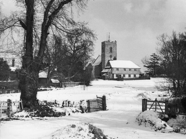 A charming winter snow scene, showing the church in the little village of Matching, Essex, England. Date: 1950s