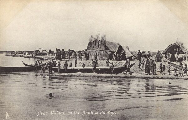 Village on the banks of the Tigris River in Iraq - showing the distinctive reed houses and boats of the Marsh Arabs of Iraq. Date: circa 1910s