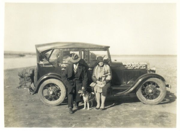 A middle aged European couple with their dog, and a car packed with suitcases, in the desert somewhere in the Middle East. There is arabic writing on the car's bonnet