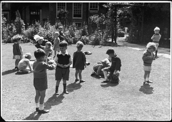 A nurse playing with a group of children on the lawn of the garden of 'The Toddlers' Evacuation Hotel&#39