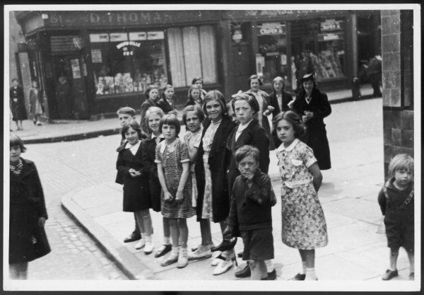 A group of evacuee children standing on a street corner