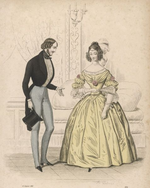 Man: black tail coat, cravat & top hat, grey strapped pantaloons, white waistcoat. Woman: gown - pointed waist, sleeves with bouffants & lace cuff & ornamented with roses