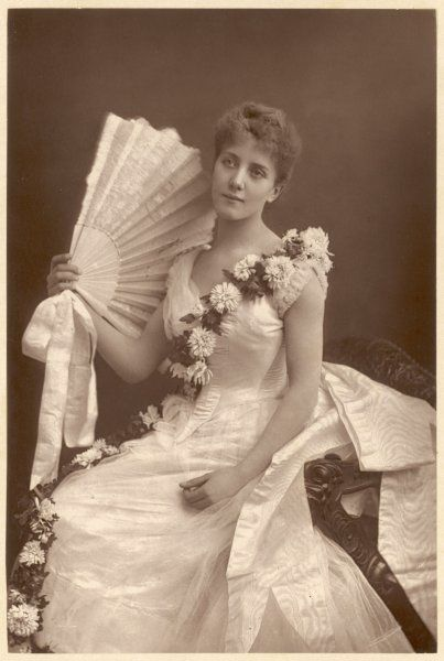 Pale sleeveless gown: pointed waist, watered silk drapery at the back, sash of chrysanthemums worn across the bodice. No jewellery but a large lace fan with ribbon bow