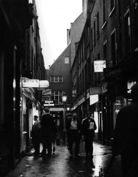 Men stroll and gaze into shop windows on an early evening in St Anne's Court, Soho, London Date: 1960s