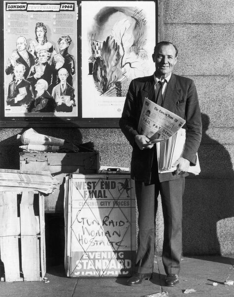 "A newspaper seller stands with a copy of The Evening Times although the placard on his stand advertising the headline from the Evening Standard ""Gun raid: woman hostage"". Date: 1962"