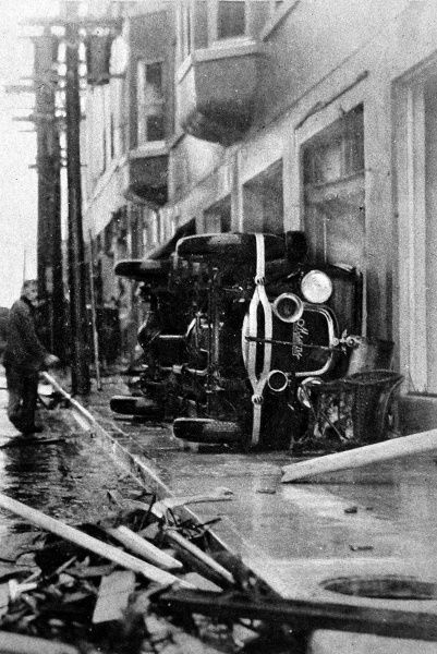 Evidence of the terrific force of the wind in North-East First Street, Miami, showing a large motor car blown onto its side (the car is possibly a Stutz)