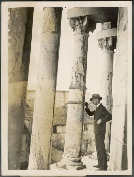 A visitor examines one of the cracked pillars of the Leaning Tower of Pisa which has been bound with steel