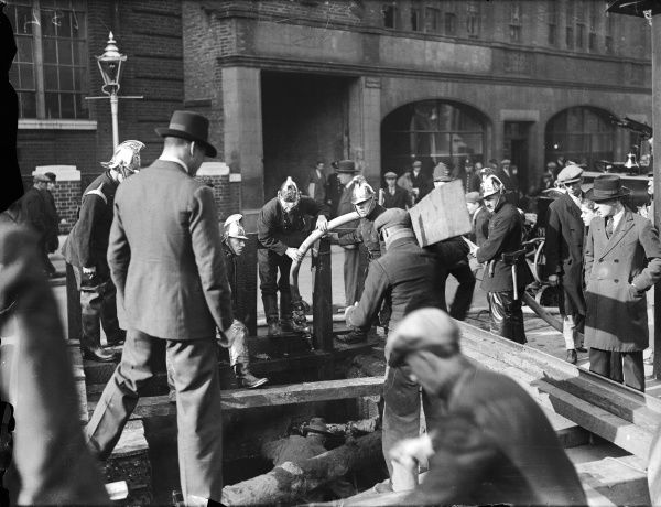 Firemen deal with an explosion in a street in Victoria, London. An interested crowd gathers to watch their progress