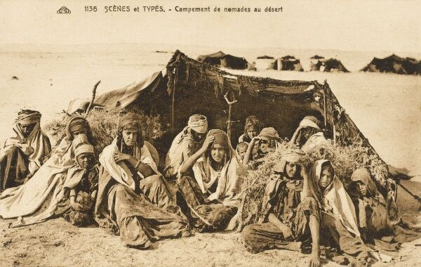 An extended family of Algerian nomadic tribespeople huddle beside their tented encampment