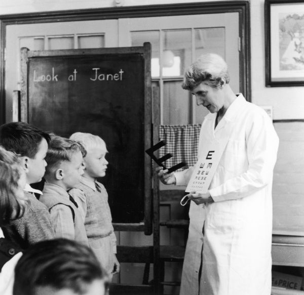 Young school children having their eyes tested by the matron