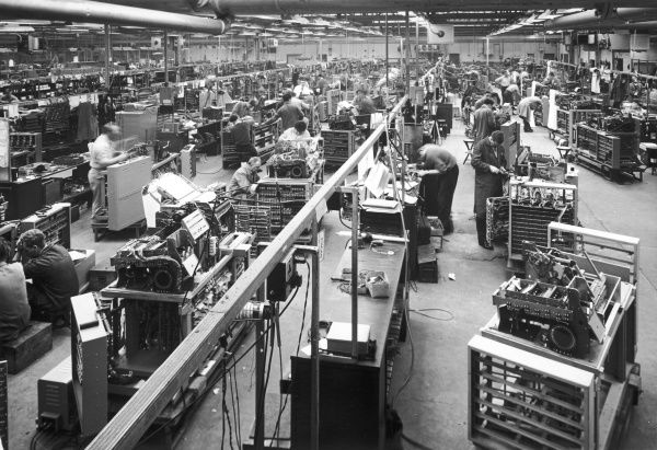 Men at work on the busy factory floor of an electronics company, assembling complicated-looking devices. Photograph by Heinz Zinram