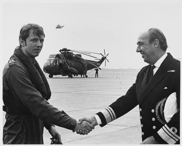 A Rear Admiral shakes hands with a Pilot as he welcomes him home from the Falklands