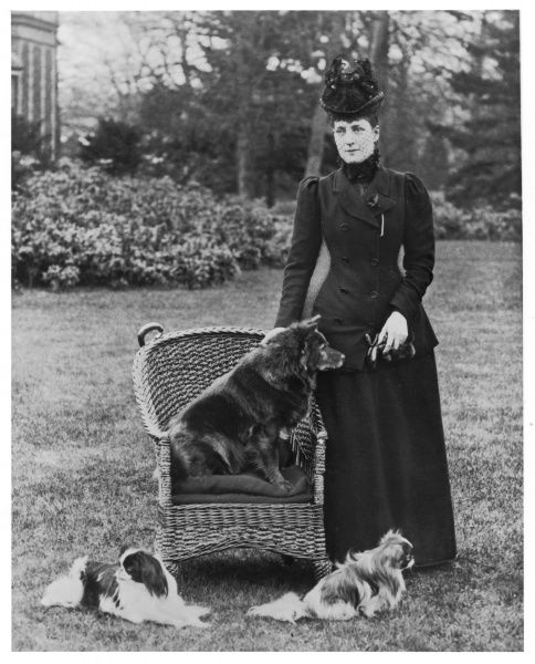 Queen Alexandra with her chow- chow Plumpy which is sitting on a wicker chair and two of her Japanese Chins, on the grass