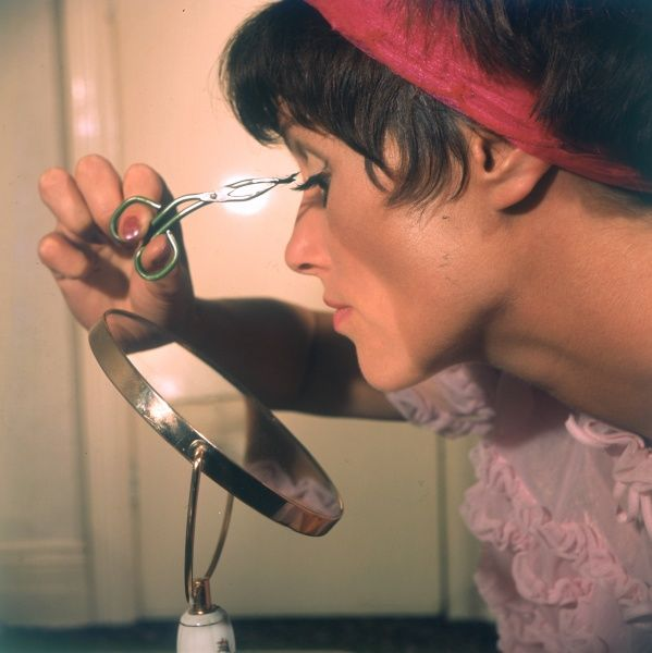 Applying false eyelashes with the aid of pincers and a magnifying make-up mirror