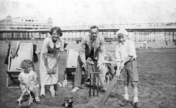 A family pose for a photograph on the beach at Weston-super-Mare in front of the Grand Pier with all their beach toys: cricket bat and stumps, a racquet and ball, bucket and spades; father smokes a pipe Date: 1920s