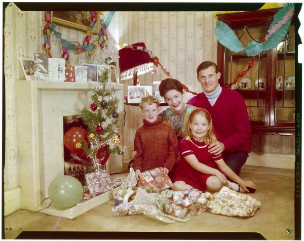 Mother, father, son and daughter pose together with their presents in front of the fireplace. Note the imitation tree, tinsel, paper chain decorations, kitsch cards &c