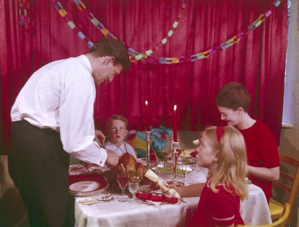 A family Christmas dinner. Father carves the turkey while his family wait expectantly