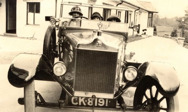 A Mother takes her two children for a spin in this beautiful and imposing open-top British sports car - a Standard Rhyl Sas. This is obviously a posed picture, as the crank handle is still in place!